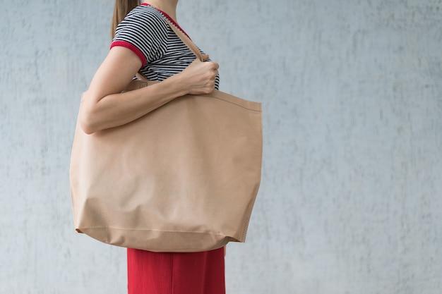 若い女性の肩に大きなエコショッピングバッグ。デザインスペース