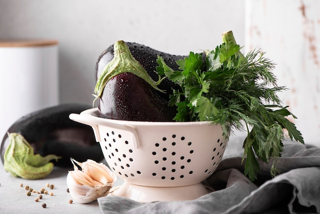 Large eggplants with garlic, parsley and dill in a white colander, close up