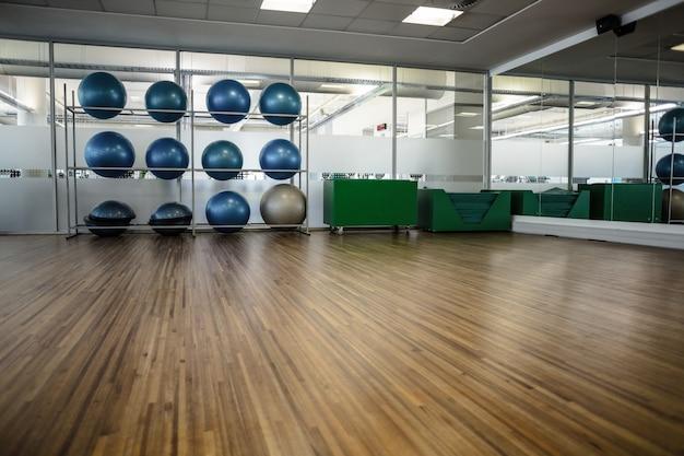 Large empty fitness studio with shelf of exercise balls