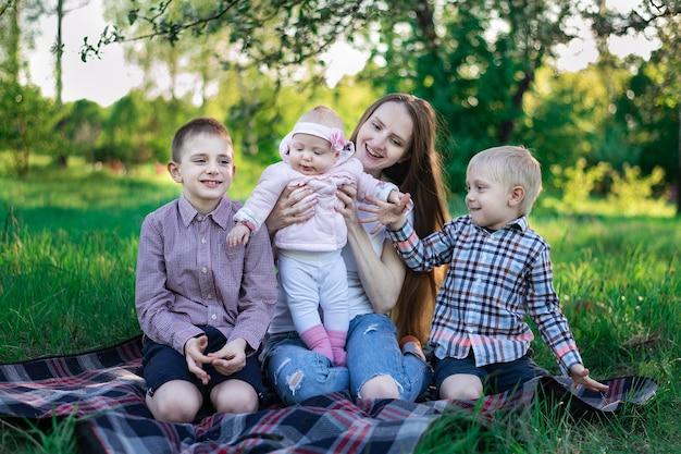 대가족. 공원에서 어머니와 세 자녀. 가족 야외 레크리에이션.