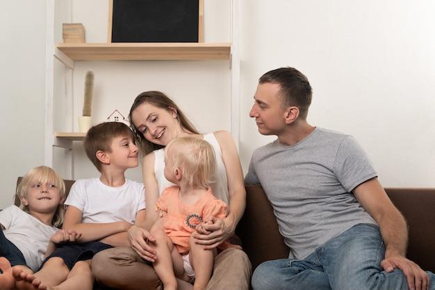 大家族の母親の父親、2人の息子と小さな娘がソファでおしゃべりしています