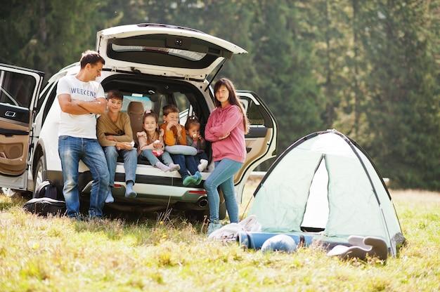 4人の子供の大家族。トランクの中の子供たち。山の中を車で旅する、雰囲気のコンセプト。アメリカの精神。