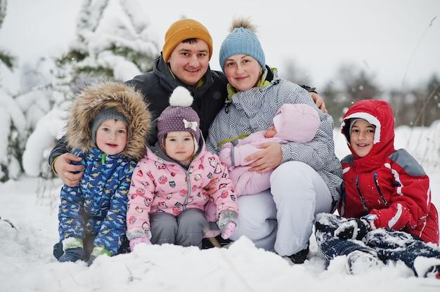 雪と降雪のある妖精の冬の日の4人の子供の肖像画の大家族。