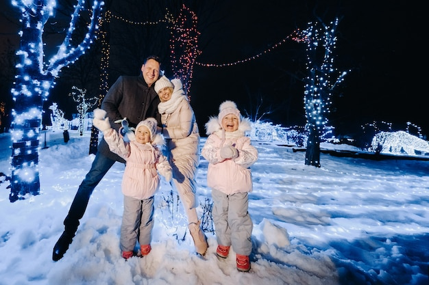 A large family with children in a christmas city at night with night lights