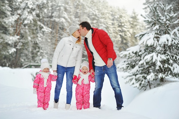 A large family with children on a walk in winter in the forest.