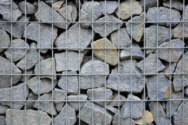 A large fence of many stone boulders supported by a stone trellis for the entire frame