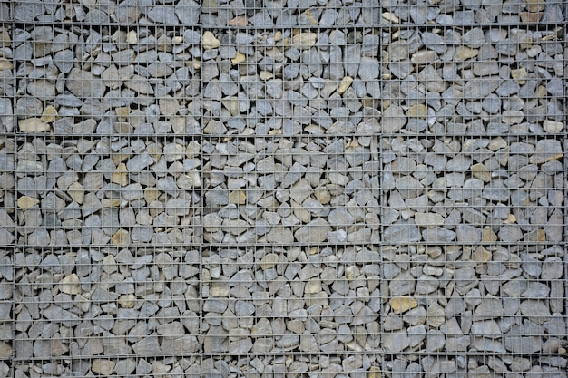 A large fence of many stone cobblestones supported by a stone trellis for the entire frame. the design takes up the entire background
