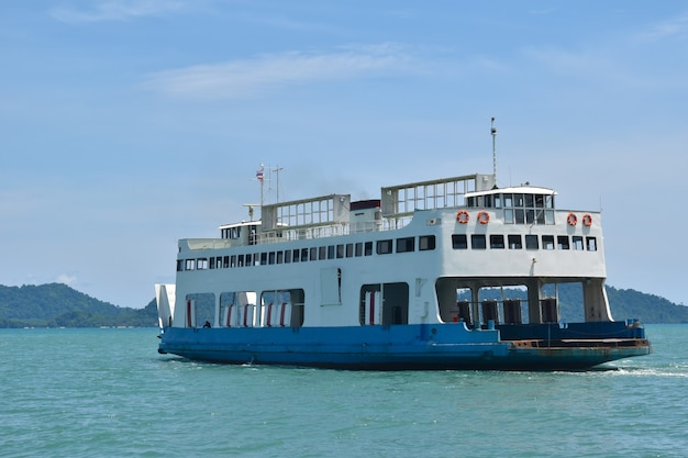 Large ferryboats carrying passengers and cars crossing in blue sea between koh chang island and trad province, thailand cargo logistics transportation delivery concept.