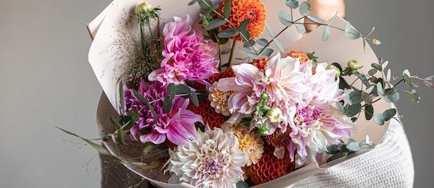 여성의 손에 국화 꽃이 든 큰 축제 꽃다발, 축제 꽃꽂이의 개념.