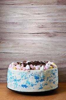 Large festive cake decorated with chocolate chips, marshmallows. copy space for inscriptions.