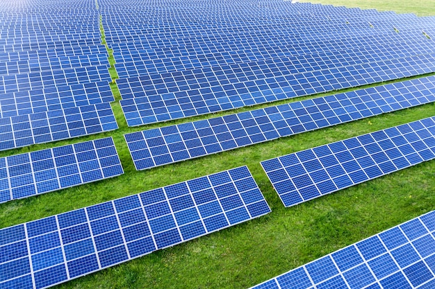 Large field of solar photo voltaic panels system producing renewable clean energy on green grass background.