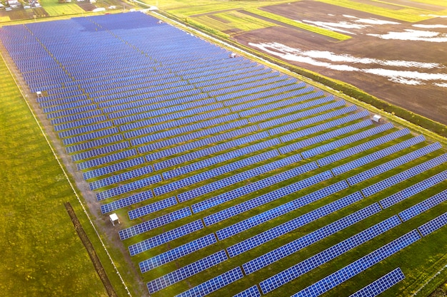 Large field of solar photo voltaic panels system producing renewable clean energy on green grass .