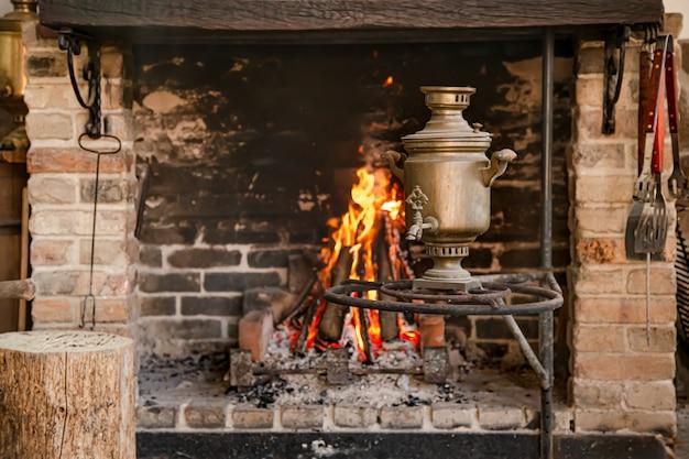 Большой камин с горящим огнем и медной самовой, уют и атмосфера.