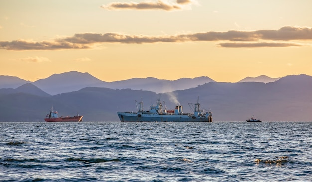 Large fishing vessel on the background of hills and volcanoes in kamchatka peninsula
