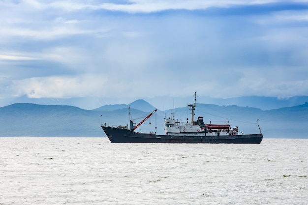 Large fishing vessel on the of hills and volcanoes