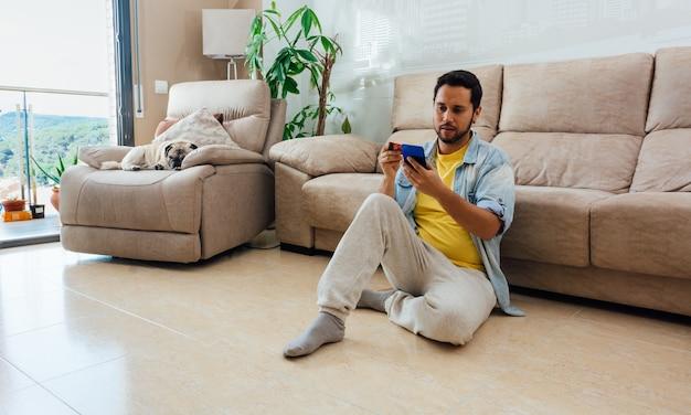 自宅の床に座って電話を使用している男性の大判ショット