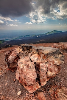 Large fractured boulder near a crater of the etna volcano in sicily. italy.