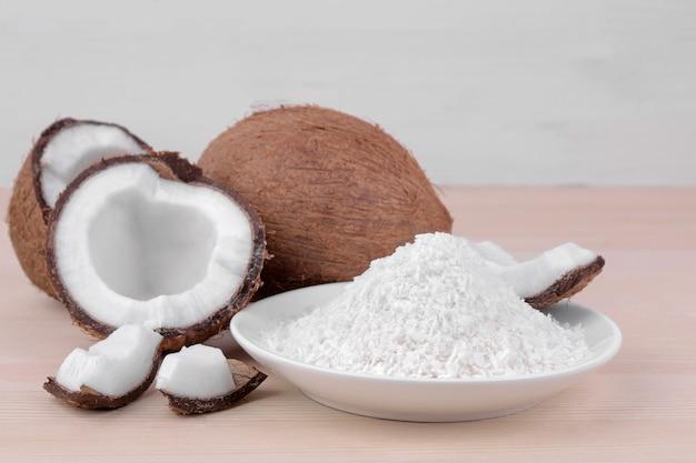 大きな新鮮なココナッツと天然木の背景にココナッツのかけら