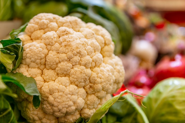 A large fresh head of cauliflower on a counter with vegetables on the market. vitamins, diet and healthy eating. close-up.