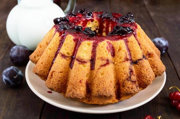 어두운 나무 테이블에 여름 딸기와 대형 갓 구운 된 케이크.
