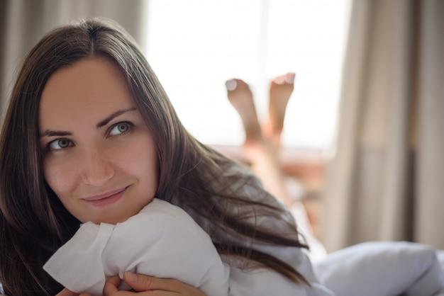 Большой фронтальный портрет одной молодой женщины в постели рано утром, проснись, доброе утро, копия пространства