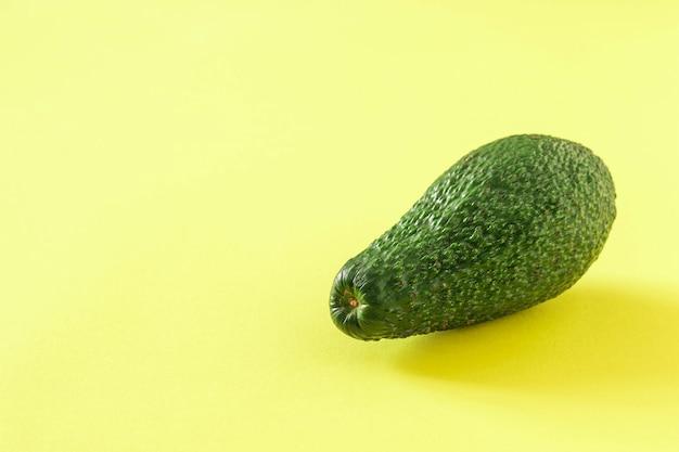 노란색 배경에 잘 익은 아보카도의 큰 과일. 맛있는 열대 야채.