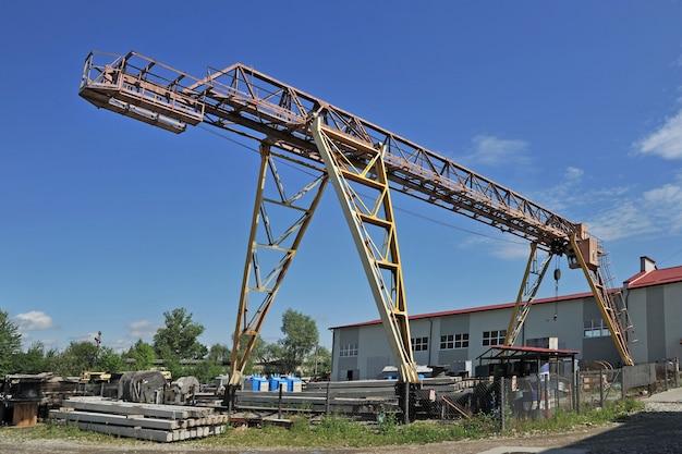 倉庫の建物と明るい青空を背景にした大型ガントリークレーン
