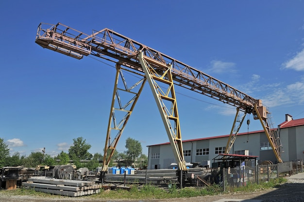 Large gantry crane against a background of warehouse buildings and of a bright blue sky