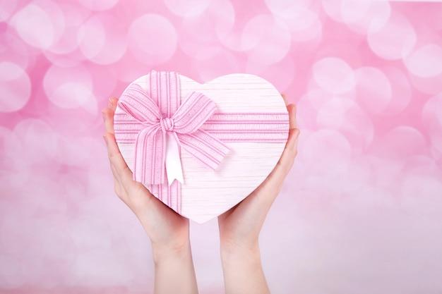 흰색 배경, 평면도에 손에 분홍색 나비와 하트 모양의 큰 선물 상자