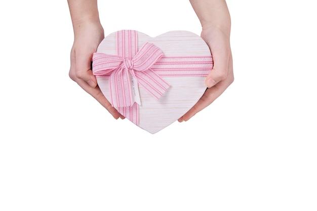 흰색 배경에 손에 분홍색 나비와 하트 모양의 큰 선물 상자