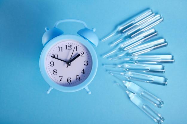 大きなガラスアンプルと青い背景の水色の目覚まし時計、コピースペース、注射の概念の時間