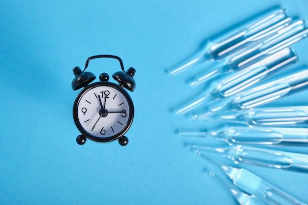 Большие стеклянные ампулы и маленький черный будильник на синем фоне, место копии, время для инъекции концепции, срок годности концепции наркотиков