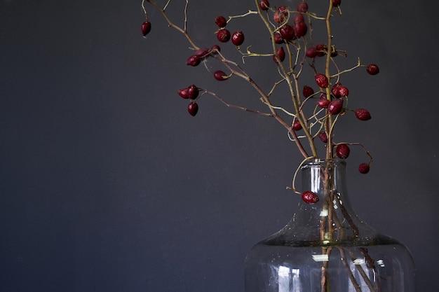 木製のテーブル、選択と集中に乾燥した赤いローズヒップの枝と大きなガラス瓶