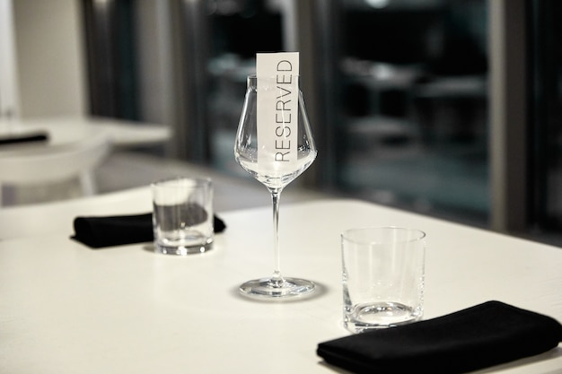 Large glass goblets with pieces of paper reserved inside, on a blurred background