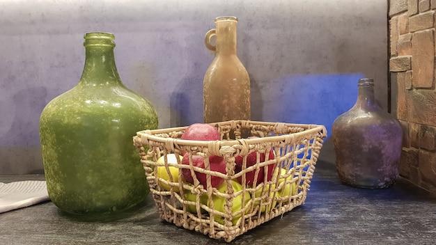 대형 유리 꽃병, 사과와 접시가 담긴 바구니가 현대적인 주방 내부에 있습니다. 디자인에서 나무와 콘크리트의 조합. 모던한 스타일의 다이닝 키친.