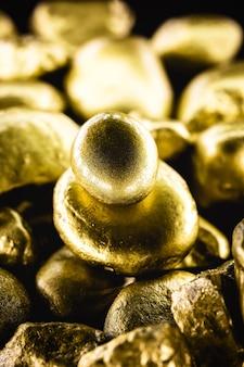 Крупный план крупных золотых камней, изолированные на черной поверхности