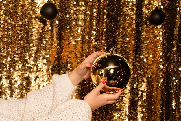 光沢のある背景の手に大きな黄金のボール