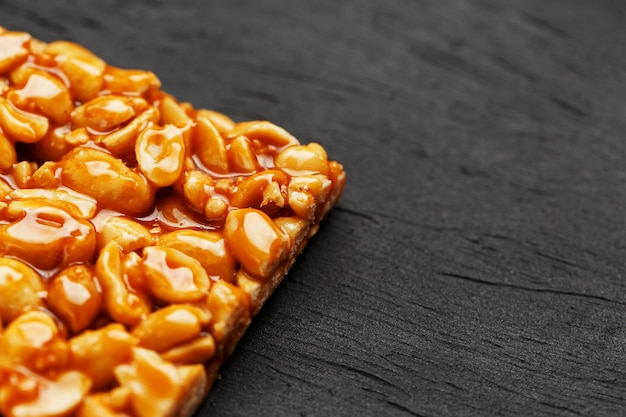 A large golden tile of peanuts, a bar in a sweet molasses. kozinaki useful and tasty sweets of the east