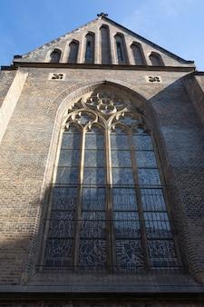 Большое готическое окно на фасаде старой католической церкви