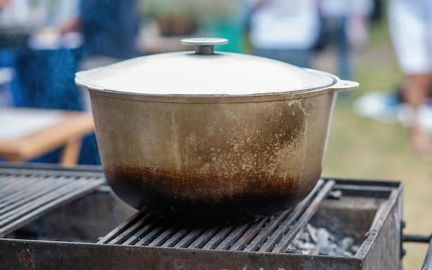 グリルの大きなねずみ鋳鉄製の大釜。キャンプファイヤーがお祭りでのテイクアウト、週末の森での休暇に備えています。