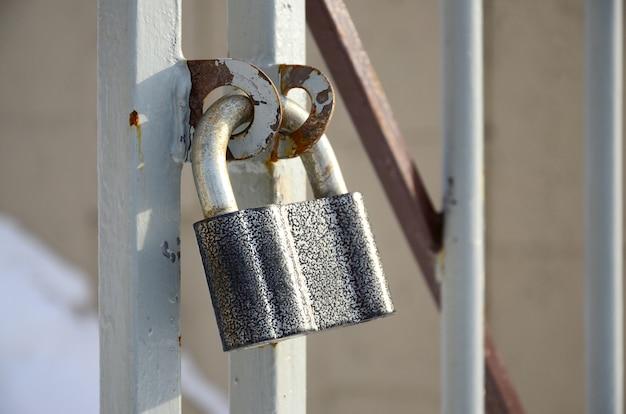 A large gray padlock hangs on a metal gate