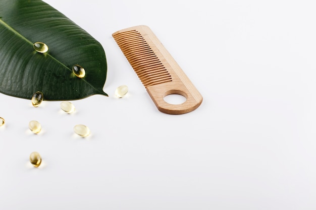 Large green leaf , wooden comb and capsules with oil lie on white table