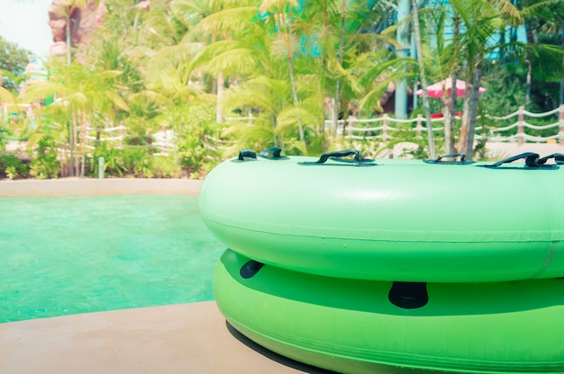 Large green swim ring for water park slide on water park pool side.