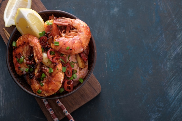 Large grilled bbq shrimp with sweet chili sauce, green onion and lemon, copyspace