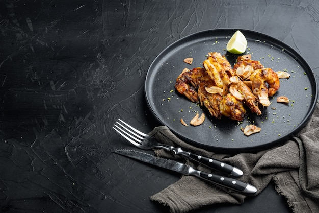 Large grilled bbq shrimp with sweet mango sauce and curry set, on plate, on black