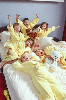Large group of friends taking good time on bed.