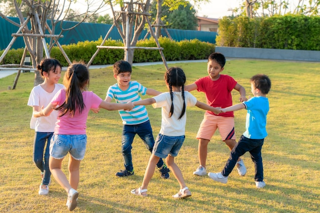 Large group of happy asian smiling kindergarten kids friends holding hands playing and dancing play roundelay and stand in circle in the park on the green grass on sunny summer day.