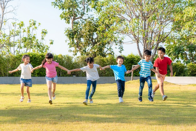 Large group of happy asian smiling kindergarten kids friends holding hands playing and running in the park on sunny summer day in casual clothes.