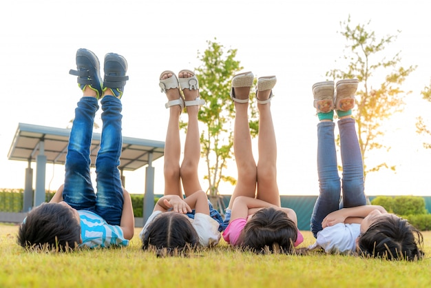 Large group of happy asian smiling kindergarten kids friends lying on grass and raised leg into sky together in the park on the green grass on sunny summer day.
