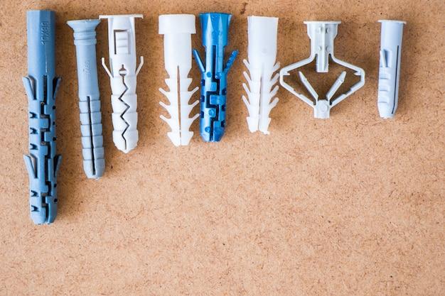 갈색 배경에 다른 플라스틱 벽 플러그의 큰 그룹, 높은 각도 보기